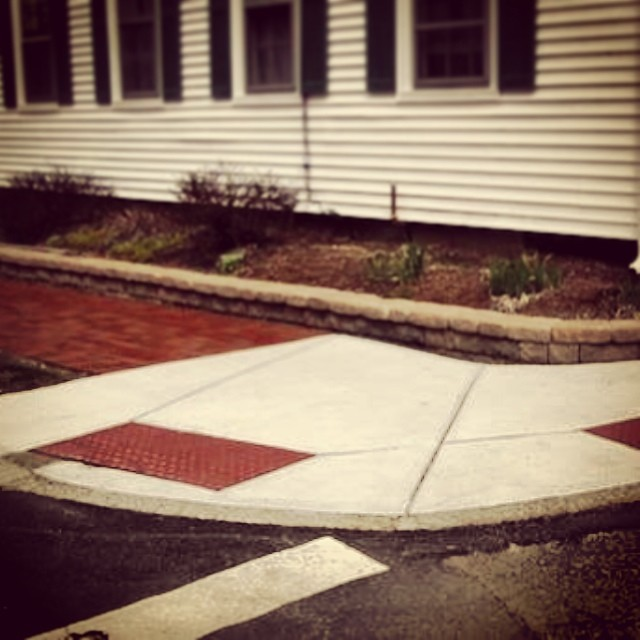 Example of new white curb cut next to a brick sidewalk.